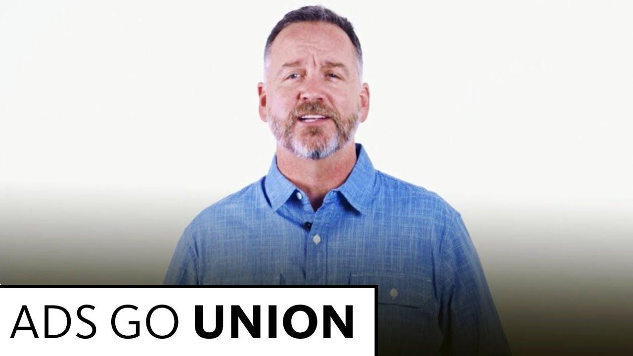 Anderson en botón azul claro hablando a la cámara con un fondo blanco.