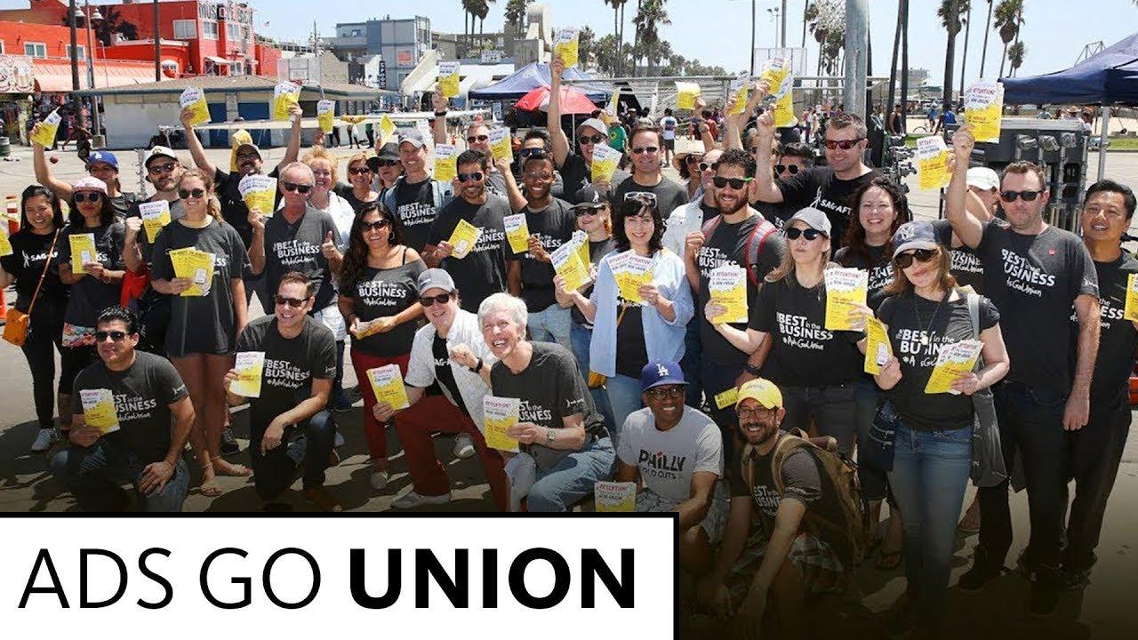 Gran grupo de personas en cuatro filas sosteniendo folletos amarillos y blancos