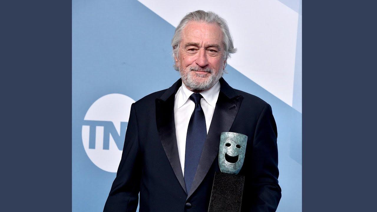 De Niro n abotonado blanco, corbata azul marino y chaqueta negra detrás del premio SAG Life Achievement Award frente a los premios SAG azules, TBS y TNT dan un paso y repiten