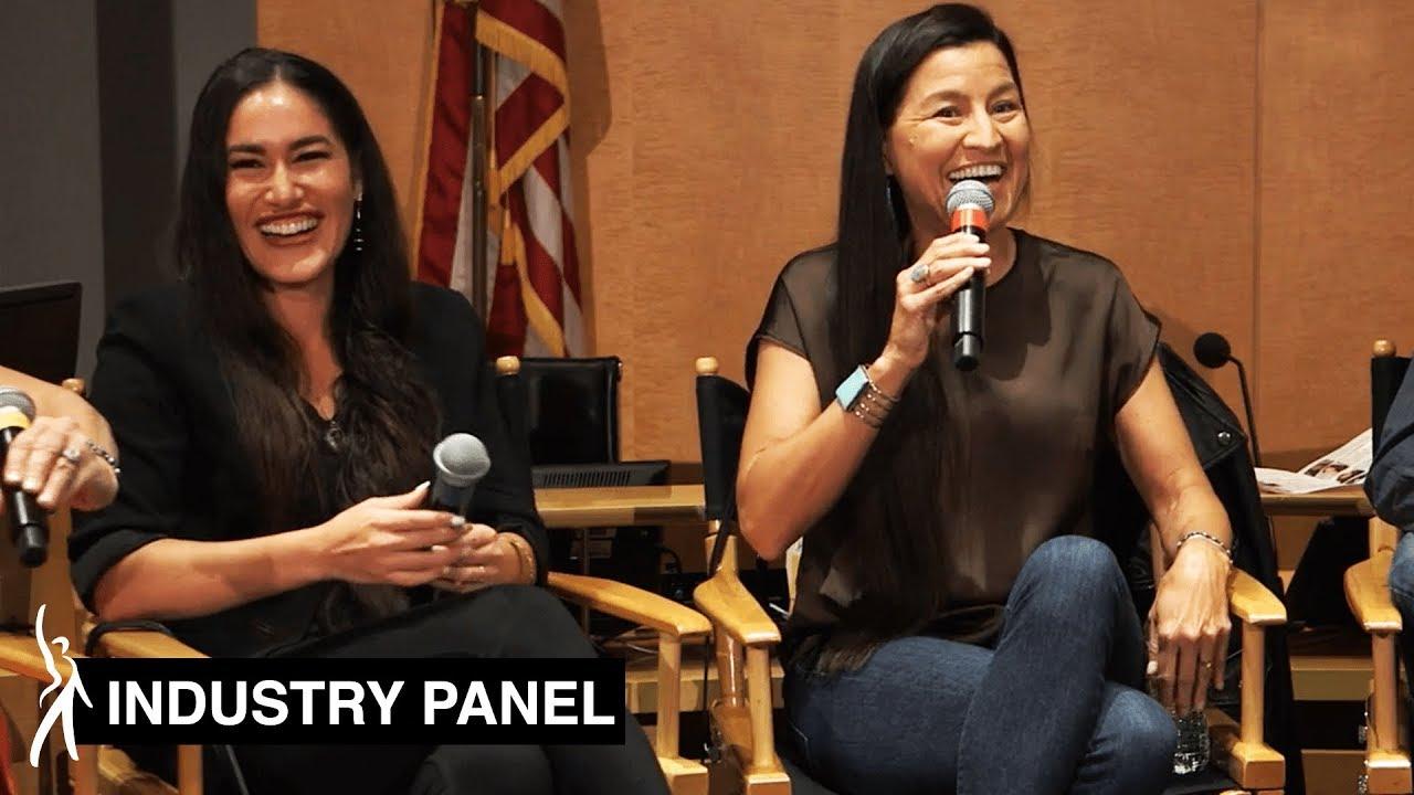 Dos mujeres panelistas sentadas en sillas de directores sosteniendo micrófonos. Panelista a la izquierda sonriendo a la audiencia mientras que panelista a la derecha habla por el micrófono mirando a la audiencia