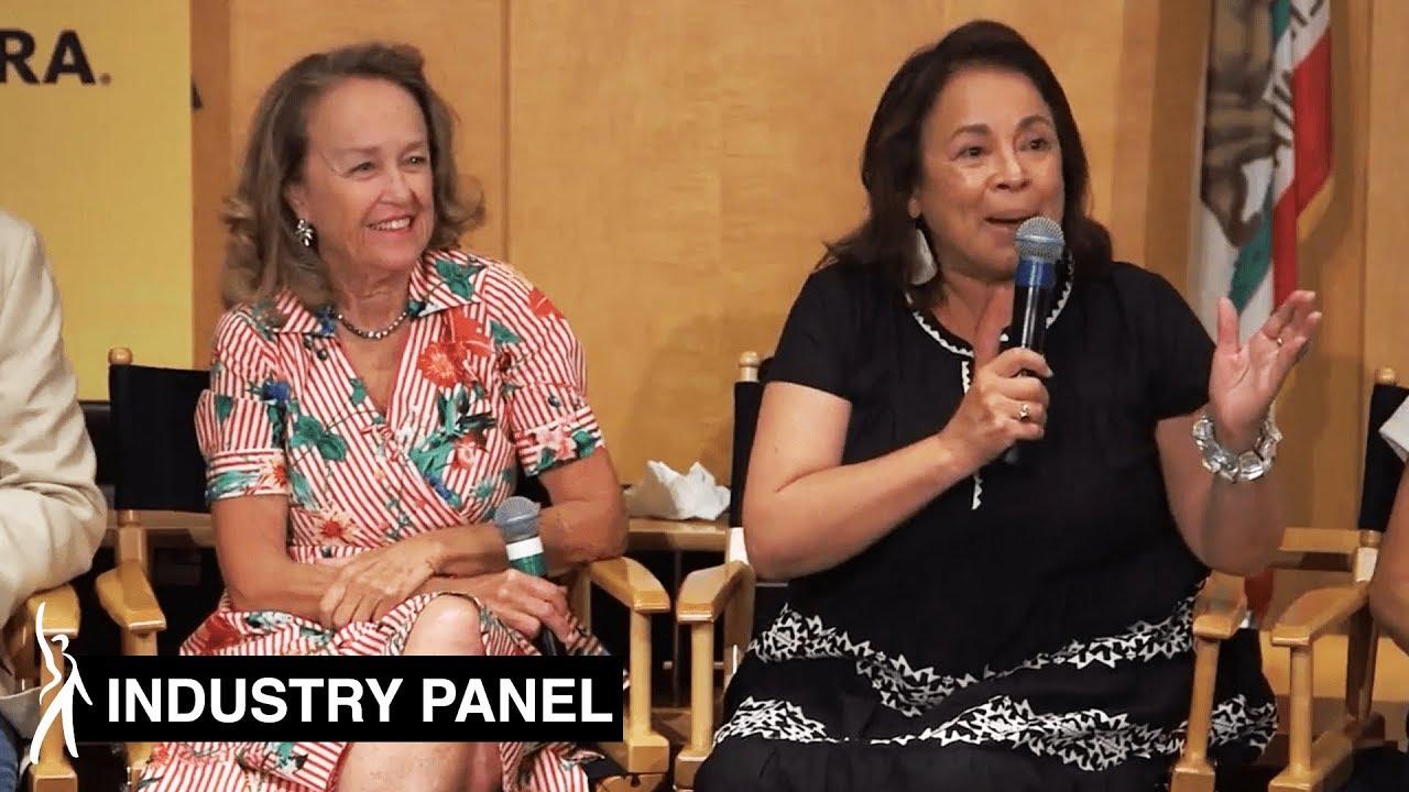 Dos panelistas sentadas una al lado de la otra en sillas de director. Panelis a la izquierda mirando a la panelista de la derecha hablando por su micrófono, mirando a la audiencia.