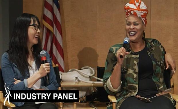 Dos panelistas sentados uno al lado del otro sosteniendo el micrófono sonriendo