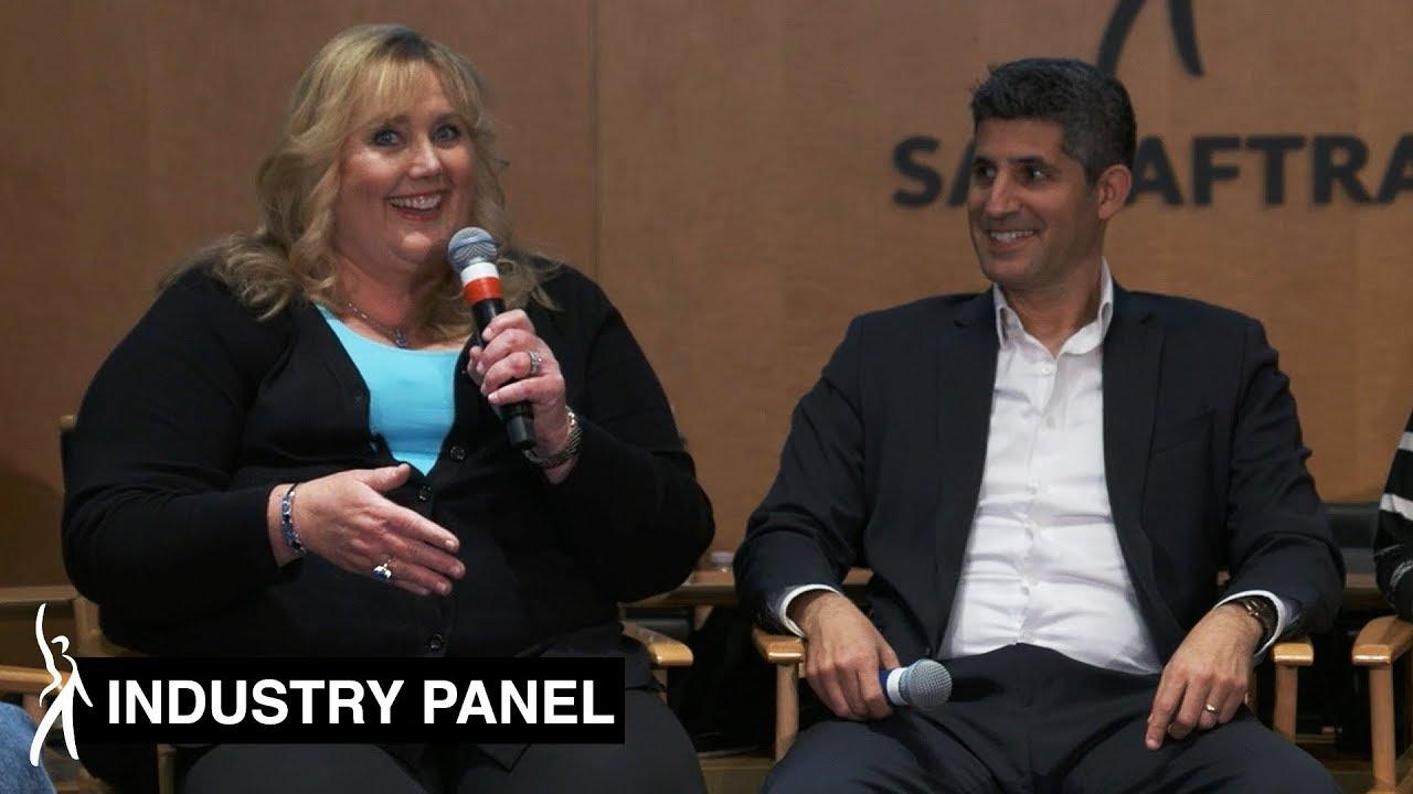 Panelista de la izquierda hablando y sonriendo en el micrófono mirando a la audiencia. El panelista de la izquierda sostiene el micrófono en la mano derecha y sonríe al panelista de la izquierda.