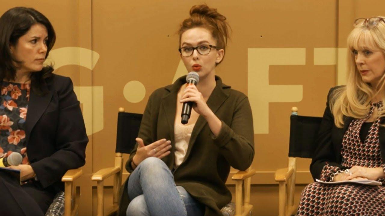 Panelista en medio hablando por micrófono con mujer de izquierda y derecha