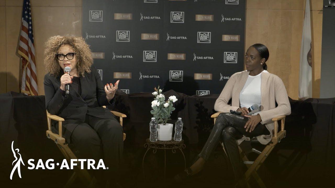 Panelista a la izquierda en una suite totalmente negra mirando a la audiencia con panelista a la derecha en top blanco y cárdigan beige y leggings negros