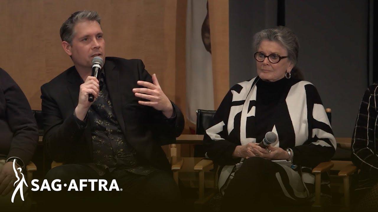 Panelista de la izquierda con camisa oscura y chaqueta negra hablando por el micrófono mirando a la audiencia. Panelista de la derecha en top negro y chaqueta de punto blanco y negro mirando a su derecha al panelista hablando.