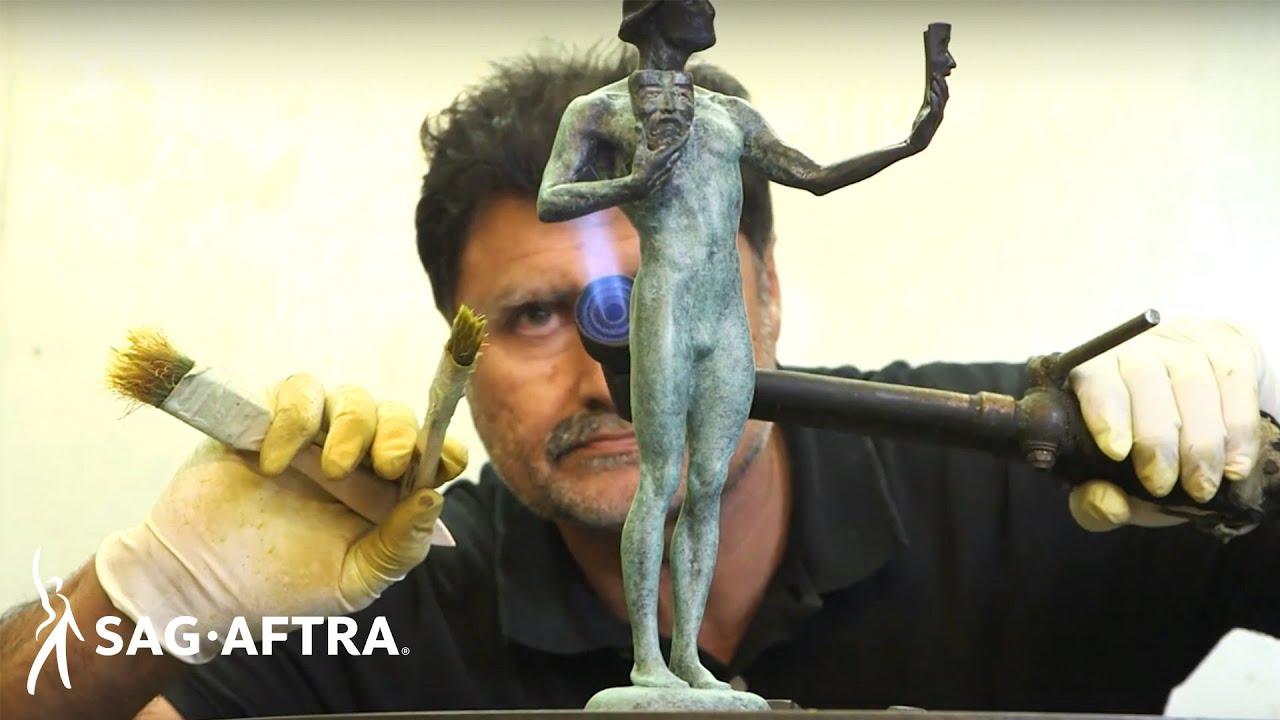 Creador del actor usando un soplete en el brazo doblado derecho del actor sosteniendo dos pinceles.