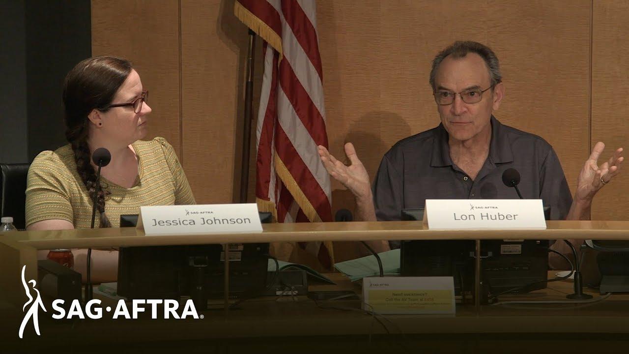 El panelista Johnson a la izquierda mira a su izquierda a Huber con una camisa de cuello gris. Tarjetas de nombre en frente de la mesa
