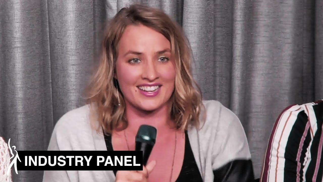 Imagen de un panelista mirando a la audiencia sonriendo sosteniendo un micrófono para hablar.
