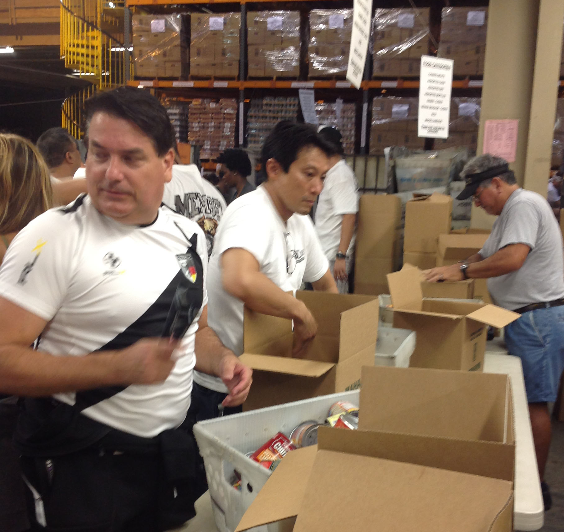 Anthony Daniel and Greg Suenaga sorting canned goods into boxes at the food drive