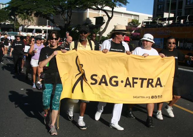 Hawaii Local SAG-AFTRA members waving our signs in the parade
