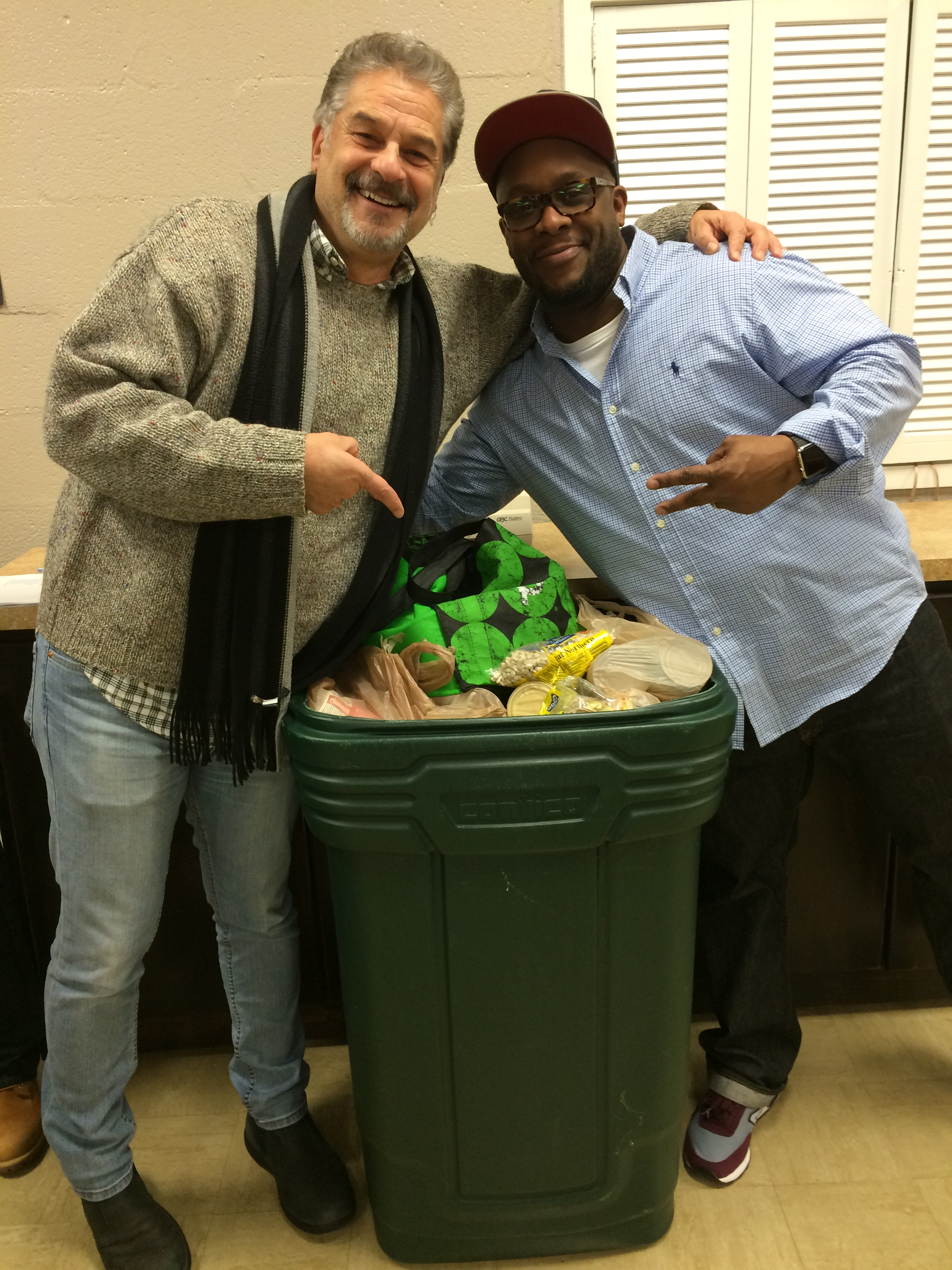 Conservatory Committee Chair Clayton Landey and Casting Director George Pierre gesture at a basketful of food donations for the Buckhead Chrtistian Ministry Food Pantry.
