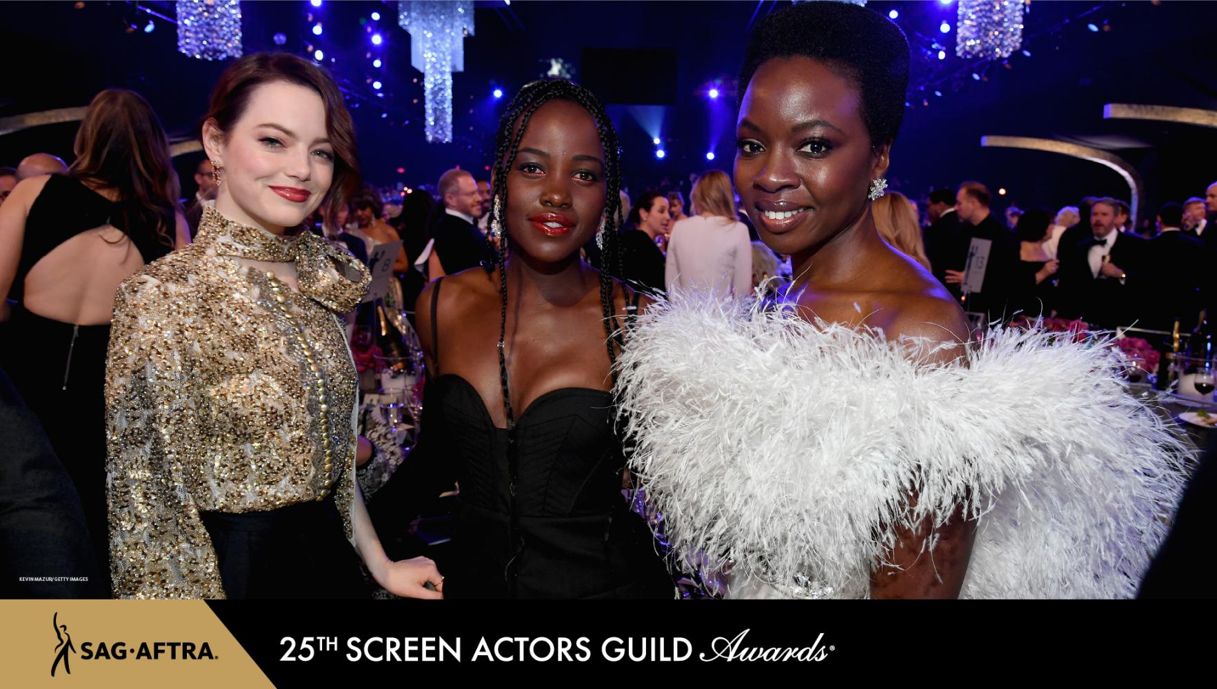 Stone in a gold beaded top, Nyong'o in a black spaghetti strap dress and Gurira in a white dress with feathers protruding around her chest