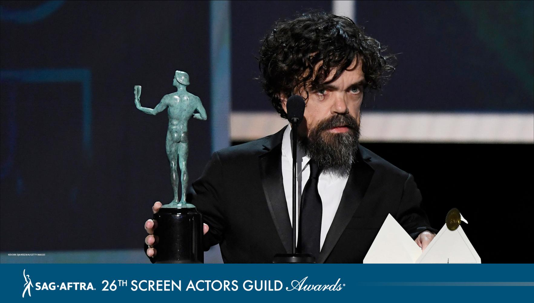 Dinklage on stage at podium with actor to his right on podium