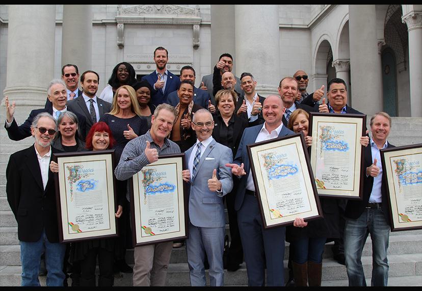 Un gran grupo de hombres y mujeres muestran certificados de reconocimiento y le dan a la cámara un gran reconocimiento.