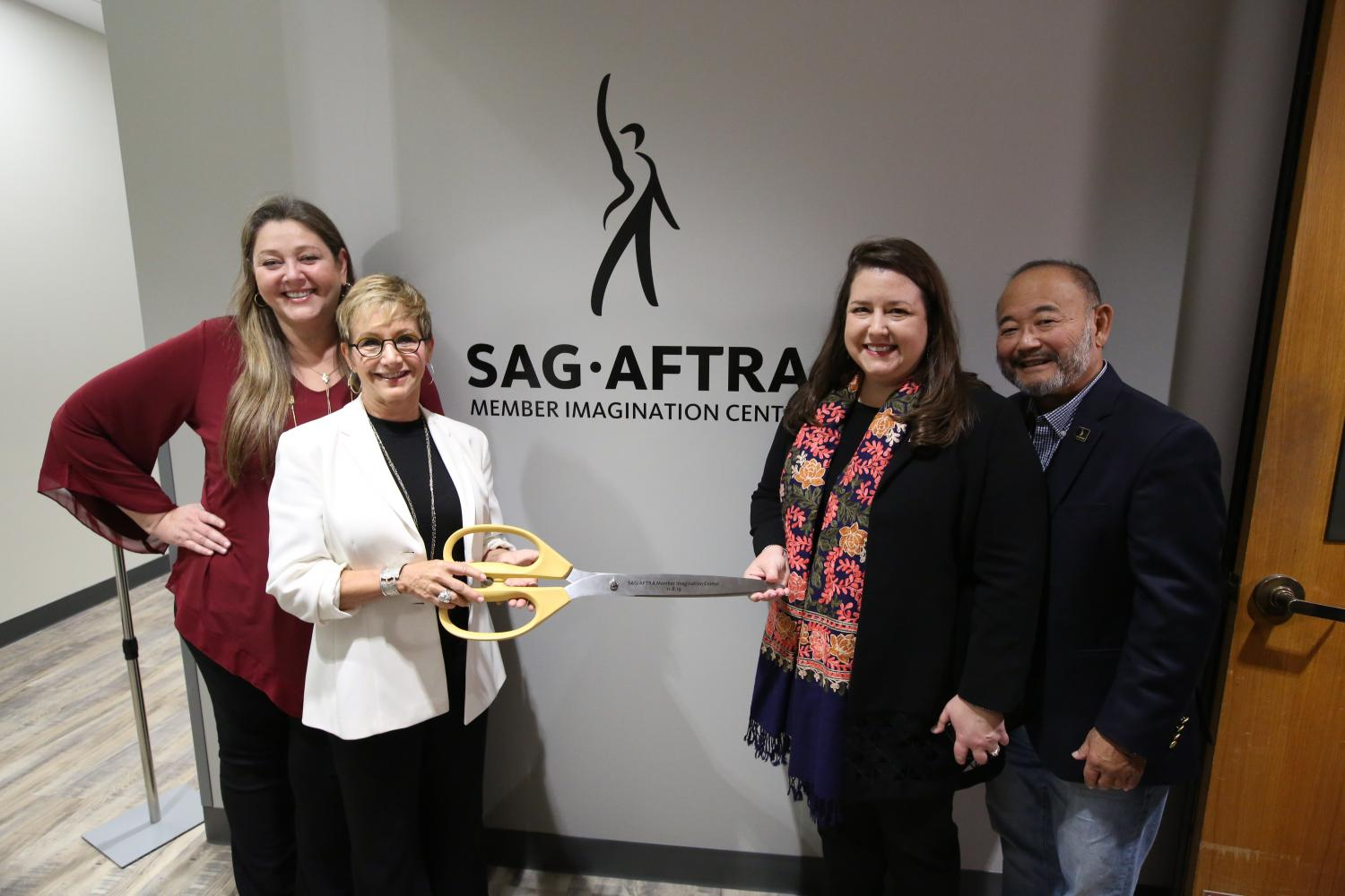 """Manheim in Maroon standing behind Carteris in black with a white blazer holding the handle of large scissors. Damon holding the opposite end of scissors wearing black and a colorful scarf with Kusatsu standing behind her. """"SAG-AFTRA Imagination Center"""""""