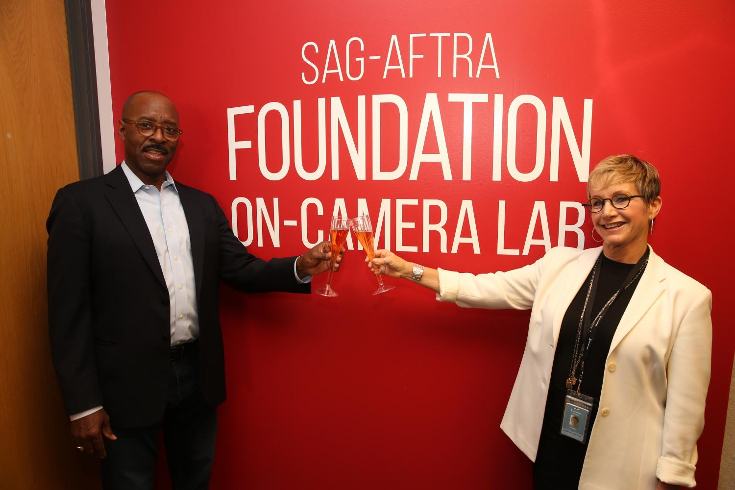 """Vance in a black suit with a light blue button up holding a champagne flute cheersing Carteris in a white blazer and black top standing in front of a red wall with the """"SAG-AFTRA Foundation"""" logo in white and """"On-Camera Lab"""" in white below the logo."""