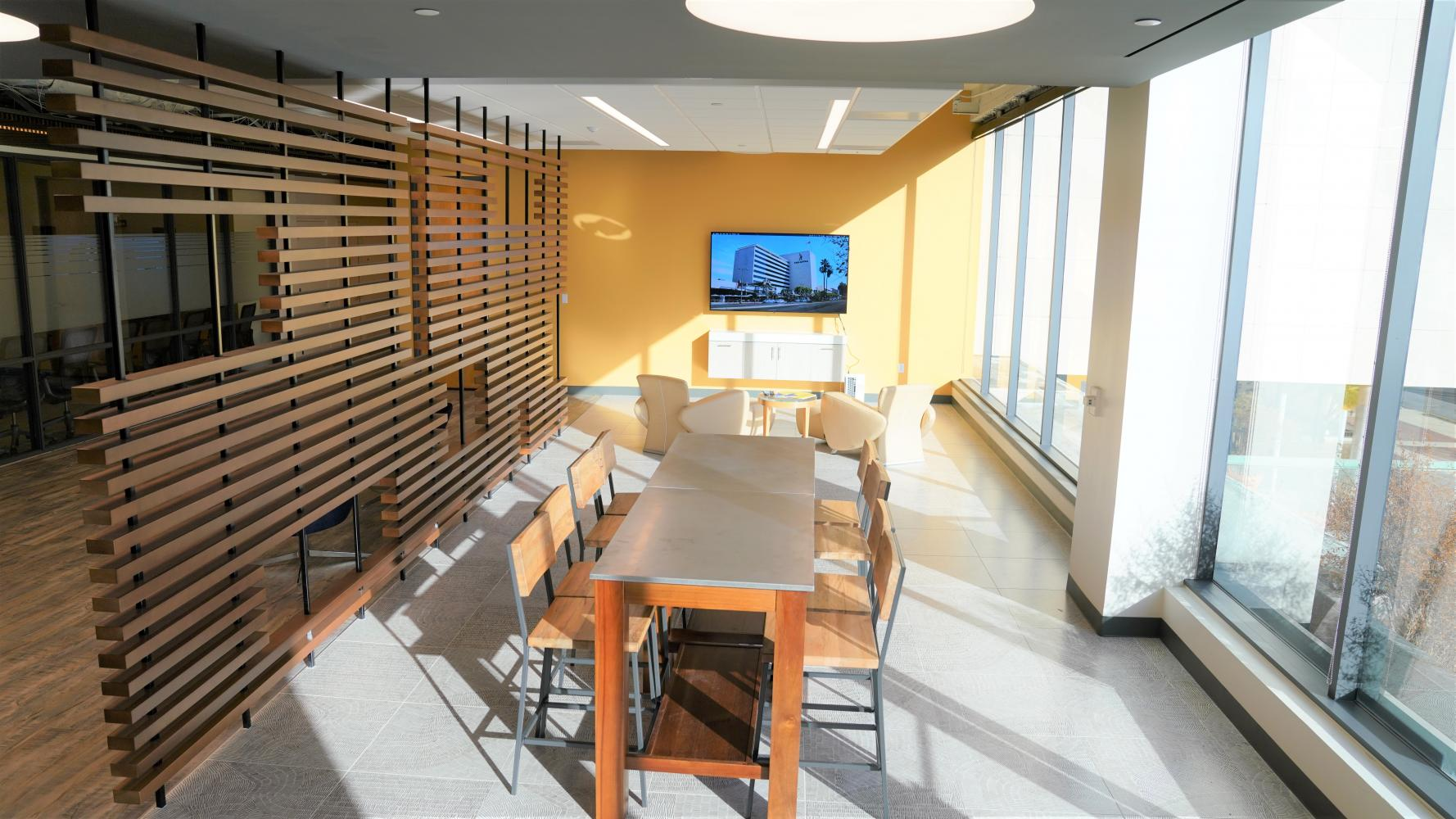 Dining Tables with 4 chairs on each side and a TV mounted on the wall
