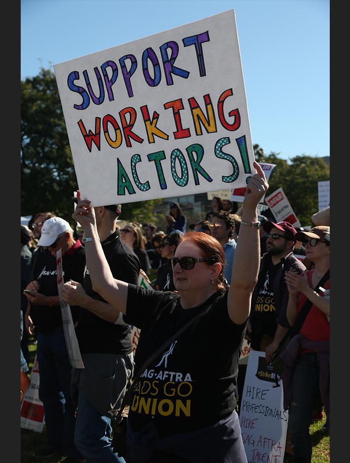 """Partidario sosteniendo un cartel de """"ACTORES TRABAJADORES DE APOYO"""" con una camiseta negra de SAG-AFTRA #AdsGoUnion."""