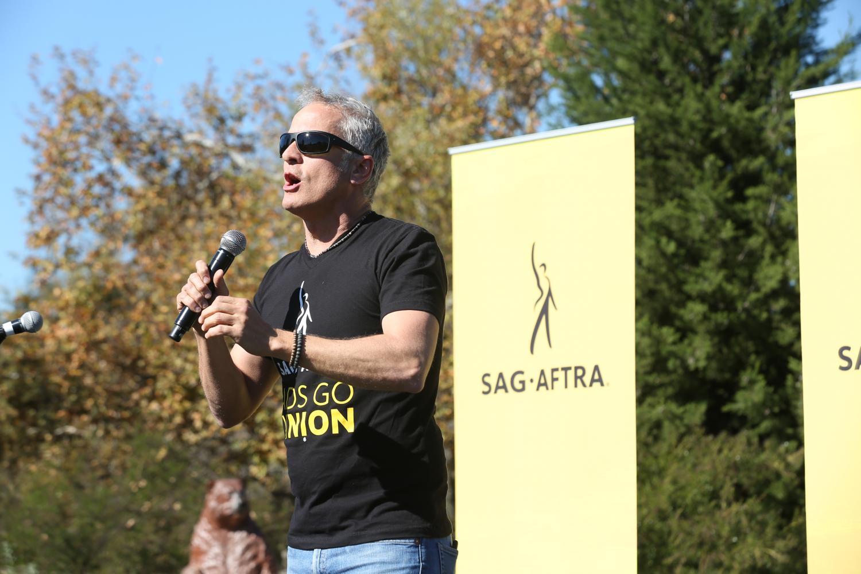 Fabian con una camisa negra SAG-AFTRA #AdsGoUnion, sosteniendo el micrófono en su mano derecha hablando a la multitud. Bandera amarilla SAG-AFTRA sobre su hombro izquierdo y árboles en el fondo.
