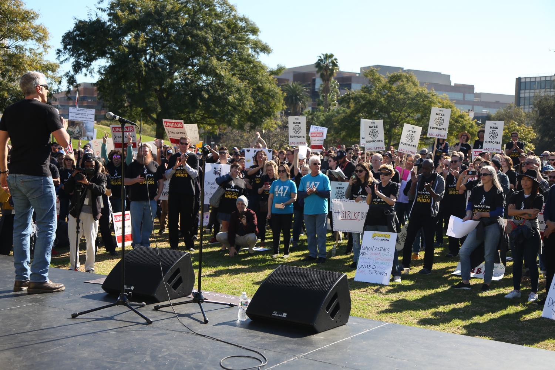 Hable en el escenario en la mitad inferior izquierda y una multitud de seguidores observando al orador desde el césped con numerosos carteles en alto.