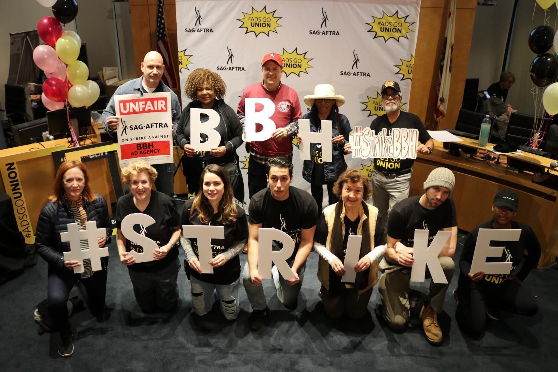 """Miembros con letras individuales de """"#StrikeBBH"""" frente a un back drop de SAG-AFTRA #AdsGoUnion"""