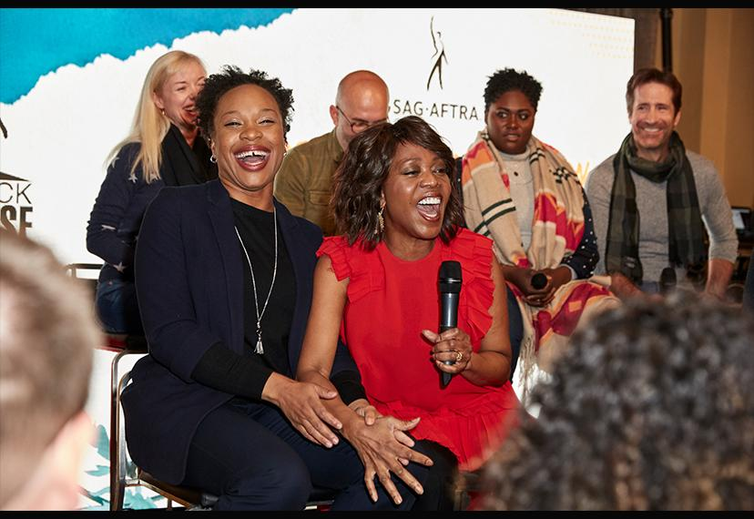 Two seated African-American women, one in blue the other in red, laugh together.