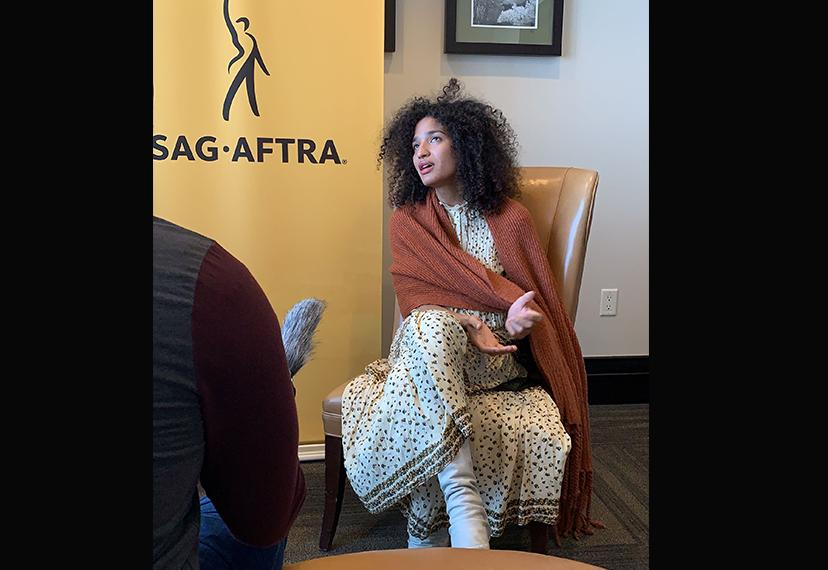 Actor Indya Moore sits in a chair with the SAG-AFTRA banner behind her.