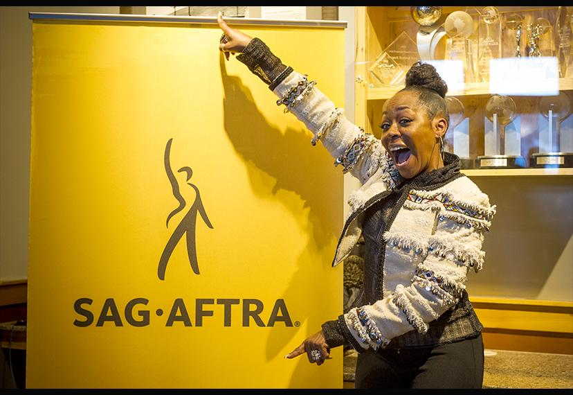 Tichina Arnold, smiling, stands beside the SAG-AFTRA banner.