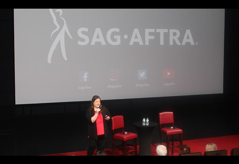 EVP and New York Local President Rebecca Damon stands on stage. Behind her, the SAG-AFTRA logo is projected unto a screen.