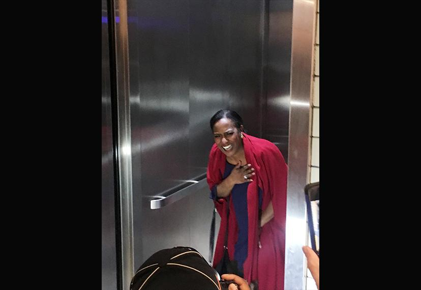 Vickie Thomas, midground, stands inside elevator. Standing in the foreground is a photographer and others holding camera phones.