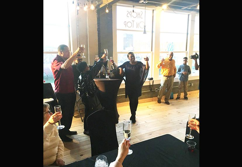 Vickie Thomas, midground center, and other individuals hold up glasses of champagnes.