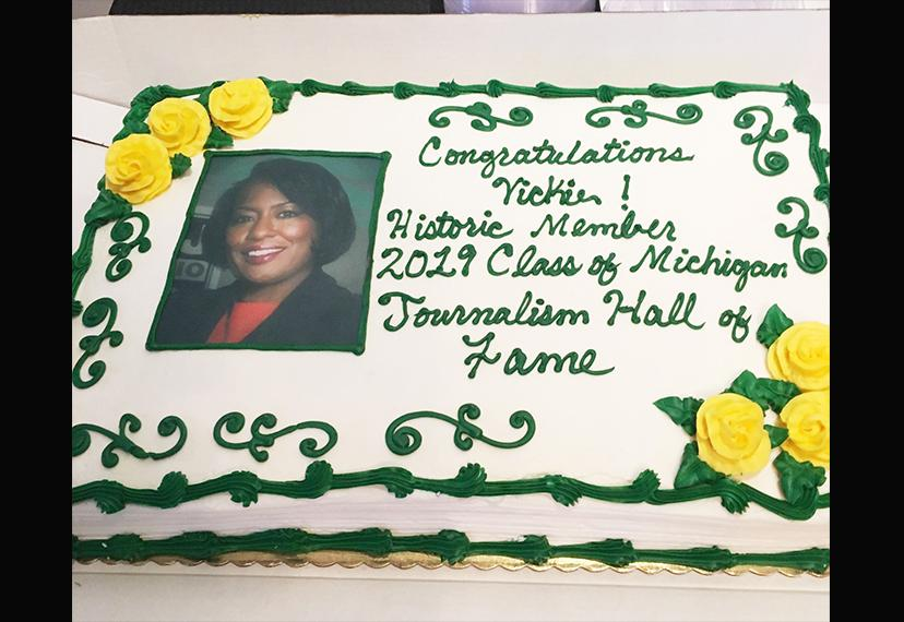 "An image of a cake with Vickie Thomas headshot and the words ""Congratulations Vickie! Historic Member 2019 Class of Michigian Journalism Hall of Fame"" in green frosting."