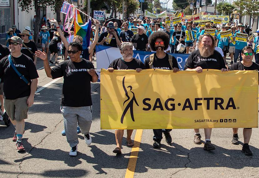 "Members wearing black ""SAG-AFTRA"" shirts walking in a parade holding a yellow SAG-AFTRA banner in front of her."
