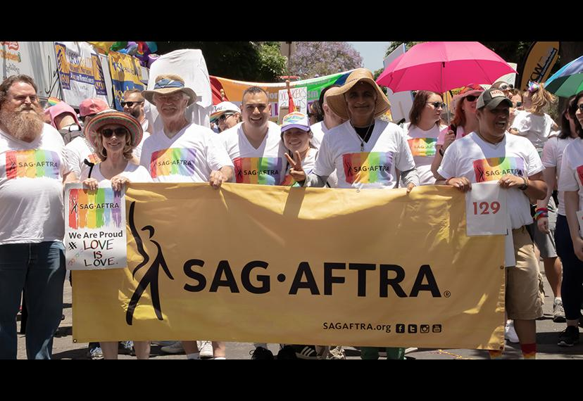Members wearing rainbow SAG-AFTRA shirts holding a yellow SAG-AFTRA banner in front