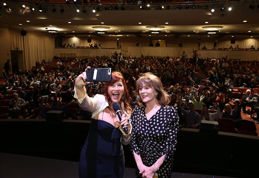 Walter in a black dress stands to Richardson's right holding a mic in left hand and phone in right. In the background is a theater with members filling all the seats