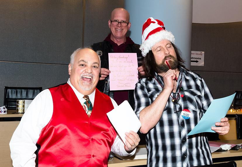Marciona in a white long sleeve button up and a red vest holds paper in left hand, Bruen wearing santa hat holding pen in right hand holding to mouth looking at paper held in left hand. Peluso stands in the middle behind Mariona and Bruen holding up pink.