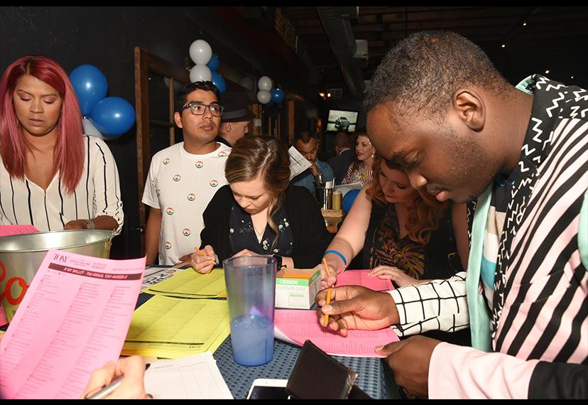 Partygoers fill out their scorecards at a table.