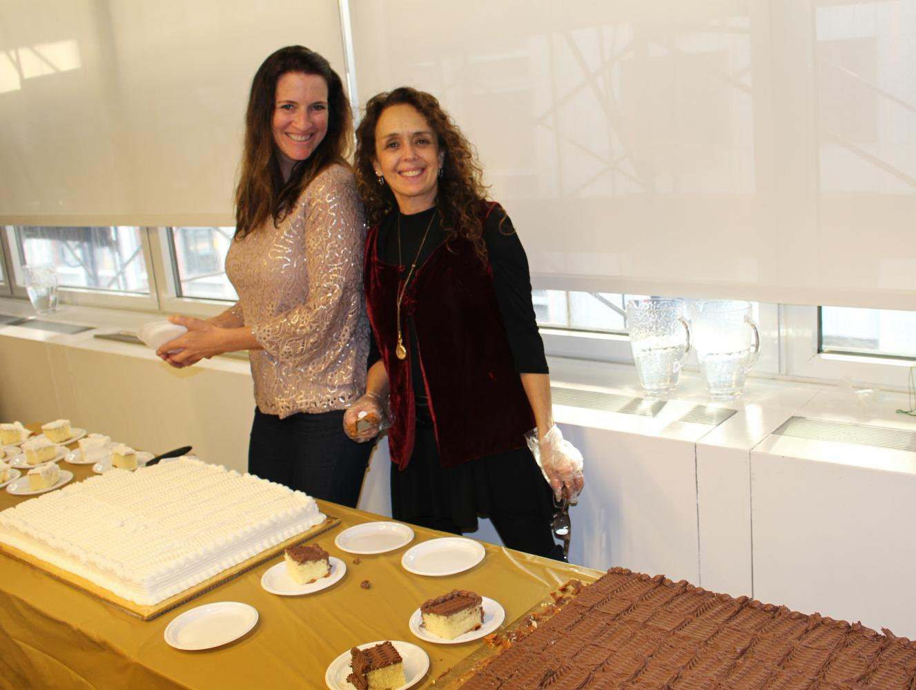 New York Host Committee members Molly Ballard and Jane Beller serve cake to members at the Holiday Open House.