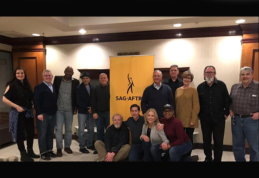 Foto grupal de miembros con sede en Cleveland con pancarta SAG-AFTRA en el centro del fondo.