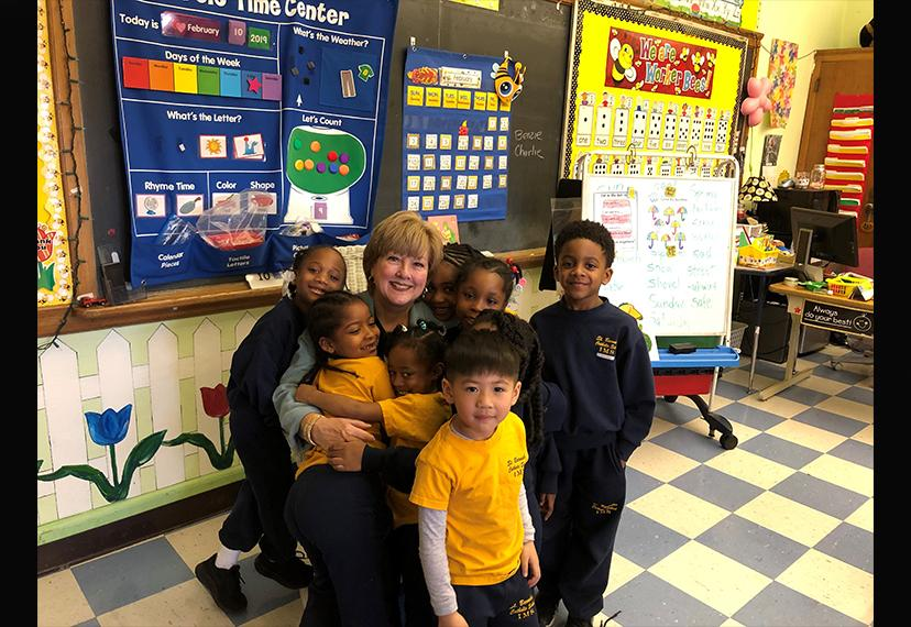 A woman is hugged by small, smiling African-American children wearing blue and yellow uniforms.