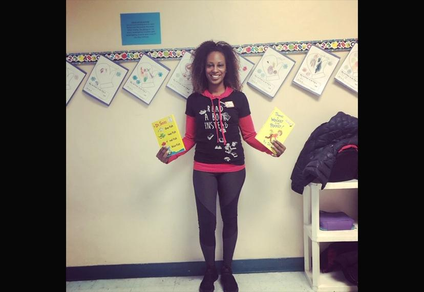 An African-American woman holds a Dr. Seuss book in each hand.