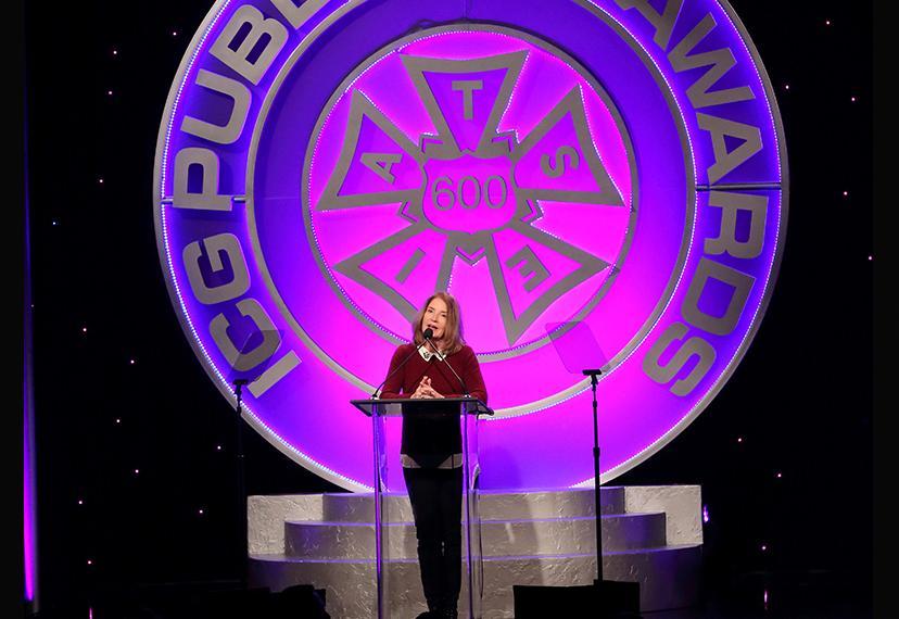 La productora ejecutiva de Screen Actors Guild, Kathy Connell, se encuentra en un podio en el escenario con el símbolo IATSE detrás de ella.