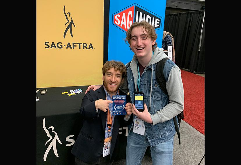 Two men take a photo with pro-union information and a digital membership card in front of the SAG-AFTRA and SAGindie backdrop.