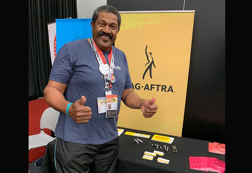 An African-American gentleman stands at a table with information about SAG-AFTRA and the union banner.