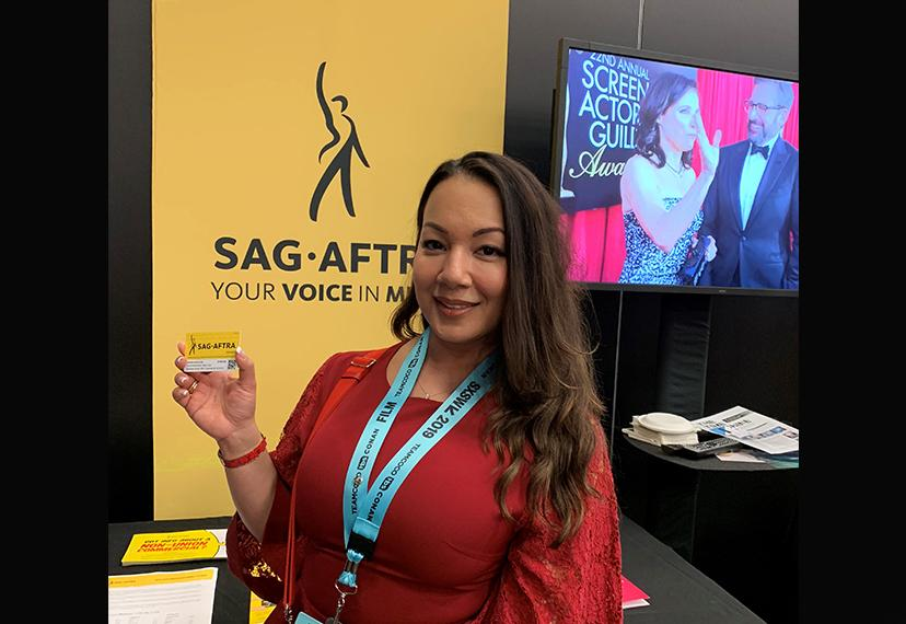 A woman in a red dress and SXSW name tag holds up her membership card.