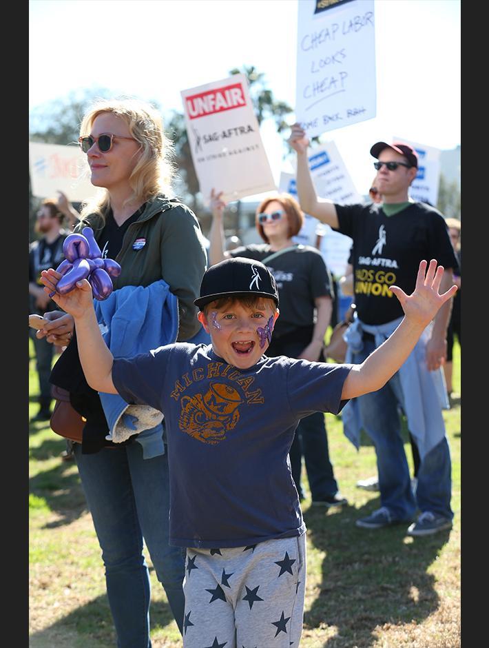 Joven, levantando las manos con entusiasmo, con un sombrero SAG-AFTRA y una camiseta azul con pantalones grises y estrellas azules oscuras