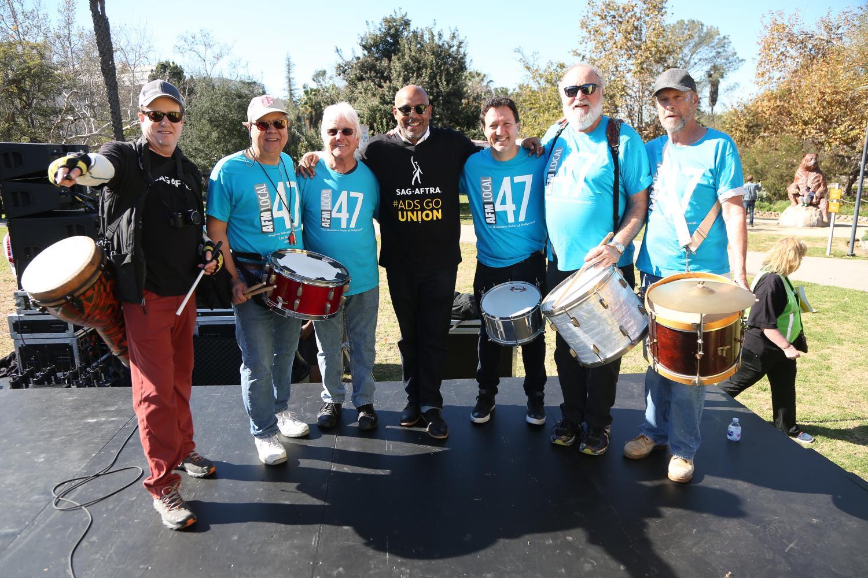 Foto grupal de 7 hombres en el escenario con sus tambores. 2 con camisas SAG-AFTRA y 5 con camisas AFM Local 47.