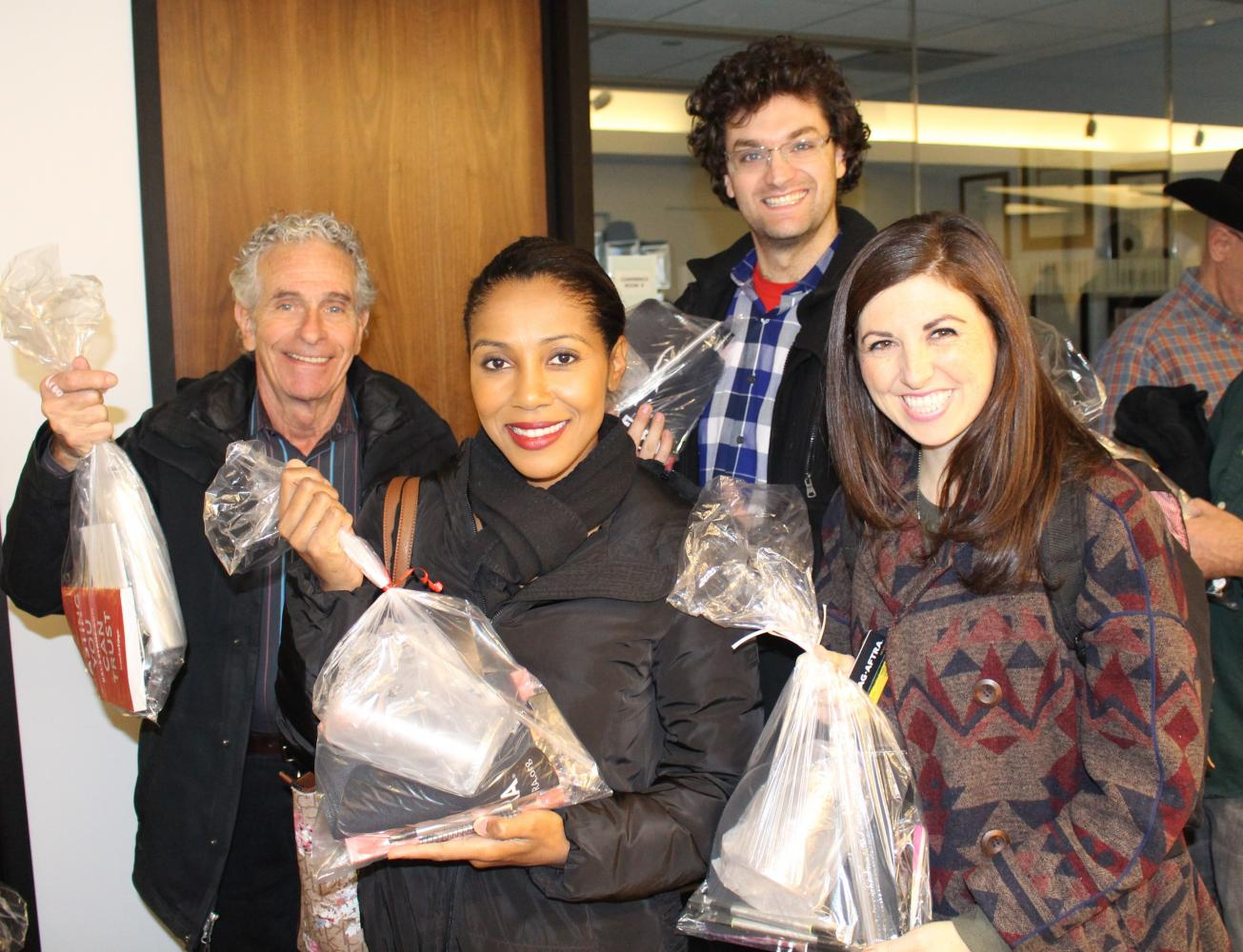 Members smile after receiving their free goody bags at the Holiday Open House.