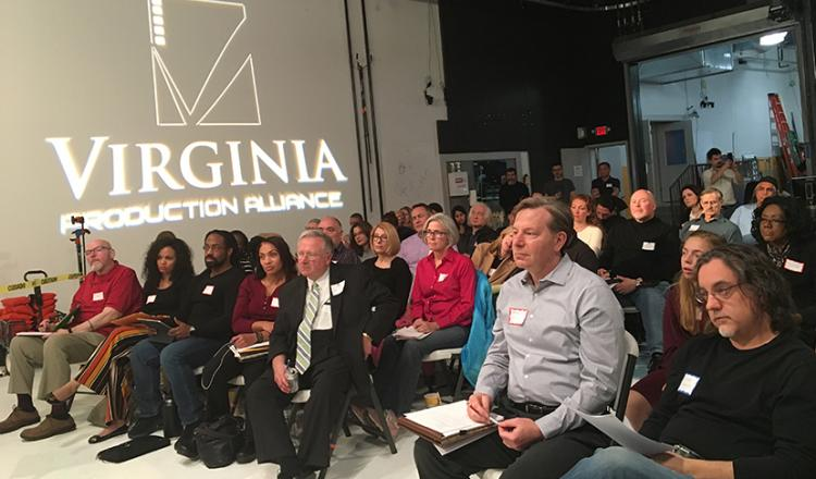 A group of men and women in seats stare offstage to the left. Behind them, the logo for the Virginia Production Alliance is projected on a screen.